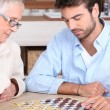Senior woman and young man playing checkers - Stock Photo
