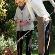Young woman helping elderly woman to do gardening — Stok fotoğraf