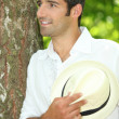 Foto Stock: Man with straw hat leaning against tree
