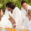 Two couples having breakfast in the garden — Stock Photo