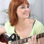 年轻的女人在打一把吉他在家里 — 图库照片 #8332112