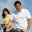 Couple enjoying a bike ride together - Stock Photo