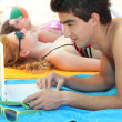 Stock Photo: Young man at the beach with his laptop