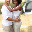 Loving couple hugging in front of their tent - Stok fotoraf