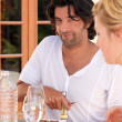 A man uncorking a wine bottle and a woman during the dinner - Stock Photo