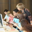 Stock Photo: Group of students looking at a computer with a teacher