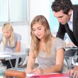Teacher helping students in the classroom — Stock Photo