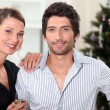 A couple behind a Christmas tree inside an apartment — Stok fotoğraf