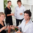 Two well dressed couples drinking sparkling wine in a living room — Stock Photo