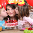 Sisters kissing mom at birthday's party - Stock Photo