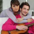 Young couple indoors with a guitar - Stock Photo