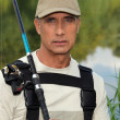 Stock Photo: Handsome middle-aged fishermby riverside