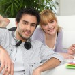 Couple at home with laptop and headphones — Stock Photo