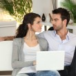 Couple relaxing on sofa with computer — Stock Photo