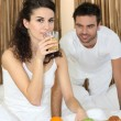 Young couple having breakfast in bed — Stockfoto