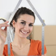 Woman holding house shaped measuring device — Stock Photo