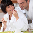 A woman giving a teaspoonful of yoghurt to his husband at breakfast, both a - Stock Photo