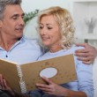 Mature couple watching a photo-album — Stock Photo