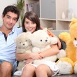 Couple sat on couch with cuddly toys - Stock Photo