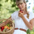 Blond woman carrying fruit basket - Stock Photo