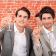 Young men in suits drinking champagne - Stock Photo