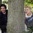 A young man dressed in coat and a young blonde woman posing near a tree — Stock Photo