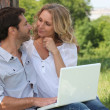 Couple with a laptop outside - Stock Photo