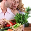 Husband showing wife vegetable basket. - Stock Photo