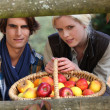 A young couple posing behind a wooden barrier with a wickerwork basket full — Stock Photo