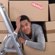 Young man surrounded by boxes moving into a new apartment — Stock Photo