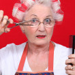 Elderly lady styling own hair — Stock Photo #8339872