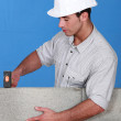 Bricklayer tapping down a block wall — Stock Photo