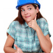 Thoughtful woman in a hardhat sitting at a desk — Stock Photo