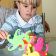 Little boy playing with a colourful toy - Stock Photo