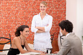 A couple dining at a restaurant and a waitress crossing her arms — Stock Photo