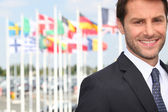 Smiling male executive in front of various flags (Bordeaux airport, France) — Stock Photo