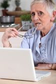 Confused old lady with laptop — Stock Photo