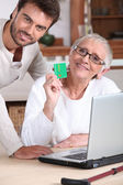 Man helping his mother keep a digital record of her healthcare expenses — Stock Photo