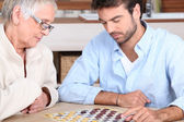 Senior woman and young man playing checkers — Stock Photo