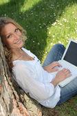 Porträtt av vackra blonda lutande mot träd arbetar på bärbar dator — Stockfoto
