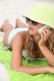 Donna posa sulla spiaggia con il telefono mobile — Foto Stock