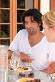 En man uncorking en vinflaska och en kvinna under middagen — Stockfoto