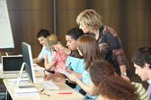 Group of students looking at a computer with a teacher — Stock Photo