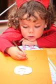Closeup of a child in a red devil's outfit drawing jack-o-lanterns — Stock Photo