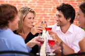 Four friends drinking in restaurant — Stock Photo