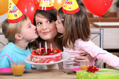 Sisters kissing mom at birthday's party — Stock Photo