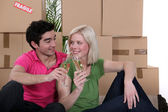 Couple having a celebratory drink on moving day — Stock Photo