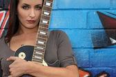 Guitarrista feminina na frente de graffiti — Fotografia Stock