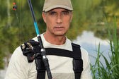 Handsome middle-aged fisherman by riverside — Stock Photo