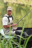Man fishing in a boat on a river — Stock Photo